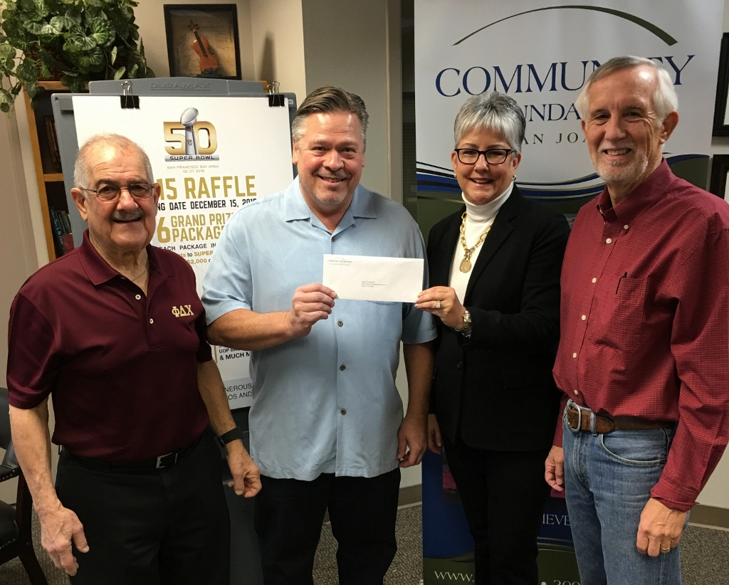 Greg Schapansky, one of six grand prize winners of the 2015 Super Bowl Raffle, receiving his Super Bowl tickets package from Linda Phillips, CEO of Community Foundation of San Joaquin, looking on are Ralph Saroyan and Ed Larimer of the Alpha Psi Foundation