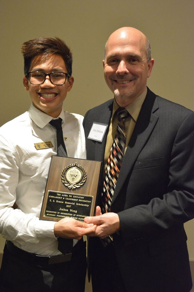 Brother Joshua Wong is presented the E.E. Roscoe Memorial Award by Director Gary DeGuire